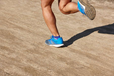 training session: Senior athletic runner leg detail. Outdoor circuit. Horizontal