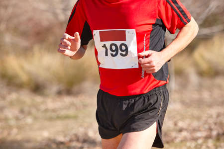 training session: Male athletic runner on a cross country race. Outdoor circuit. Horizontal