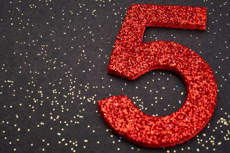age 5: Number five red color over a black background. Anniversary. Horizontal