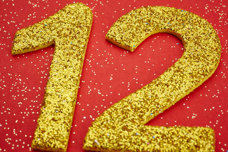 twelve: Number twelve yellow color over a red background. Anniversary. Horizontal