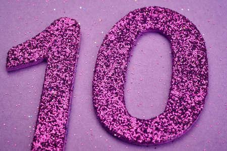 numero diez: El número diez de color púrpura sobre un fondo de color púrpura. Aniversario. Horizontal Foto de archivo