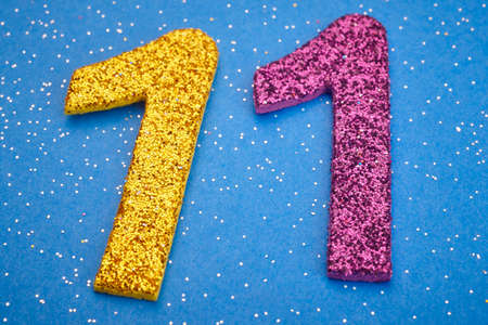 number 11: Number eleven yellow purple color over blue background. Anniversary. Horizontal