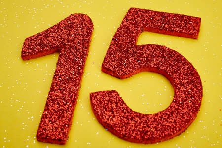 fifteen: Number fifteen red color over a yellow background. Anniversary. Horizontal
