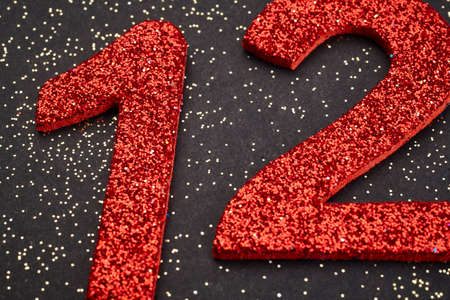 number twelve: Number twelve red color over a black background. Anniversary. Horizontal