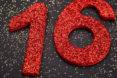 sixteen: Number sixteen red color over a black background. Anniversary. Horizontal Stock Photo