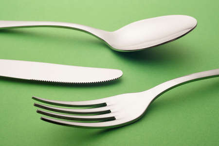 fork knife spoon: Fork knife spoon detail over a green background. Cutlery. Horizontal