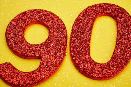 ninety: Number ninety red color over a yellow background. Anniversary. Horizontal
