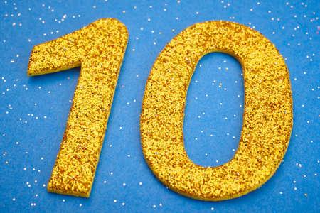 numero diez: El número diez de color amarillo sobre un fondo azul. Aniversario. Horizontal Foto de archivo