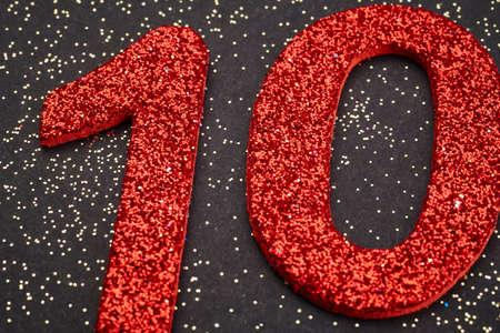 numero diez: El número diez de color rojo sobre un fondo negro. Aniversario. Horizontal