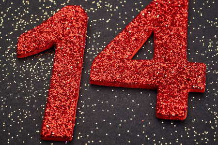 fourteen: Number fourteen red color over a black background. Anniversary. Horizontal Stock Photo