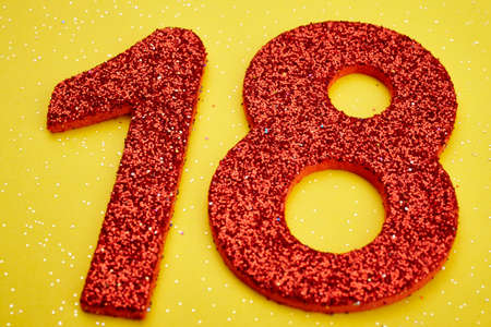 eighteen: Number eighteen red color over a yellow background. Anniversary. Horizontal
