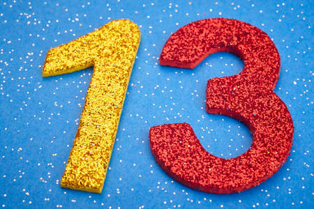 thirteen: Number thirteen yellow red color over blue background. Anniversary. Horizontal Stock Photo