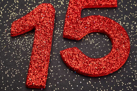 fifteen: Number fifteen red color over a black background. Anniversary. Horizontal Stock Photo