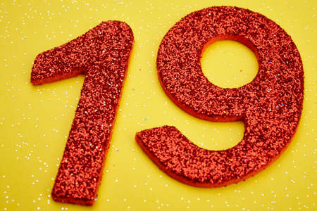 nineteen: Number nineteen red color over a yellow background. Anniversary. Horizontal