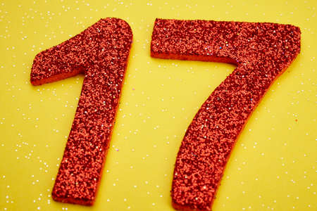 seventeen: Number seventeen red color over a yellow background. Anniversary. Horizontal Stock Photo
