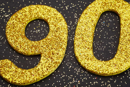 ninety: Number ninety golden color over a black background. Anniversary. Horizontal