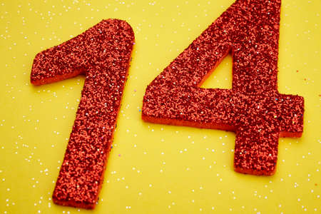 fourteen: Number fourteen red color over a yellow background. Anniversary. Horizontal Stock Photo
