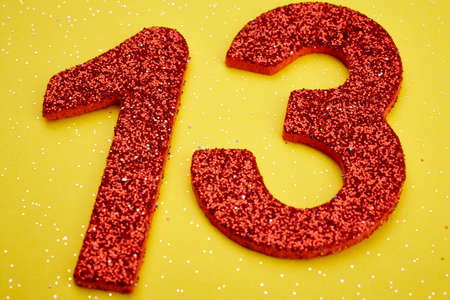 thirteen: Number thirteen red color over a yellow background. Anniversary. Horizontal