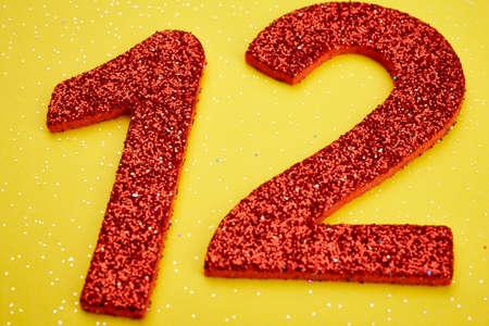 Número doce de color rojo sobre un fondo amarillo. Aniversario. Horizontal Foto de archivo - 56289250