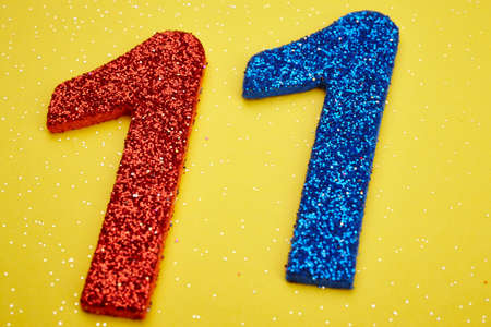 number 11: Number twelve red blue over a yellow background. Anniversary. Horizontal