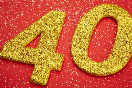 forty: Number forty golden color over a red background. Anniversary. Horizontal