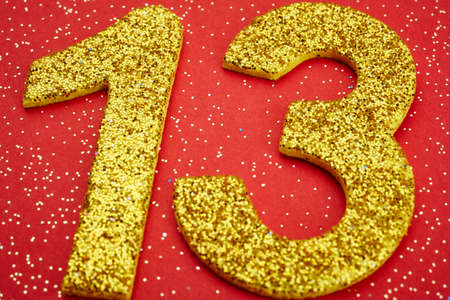 thirteen: Number thirteen yellow color over a red background. Anniversary. Horizontal