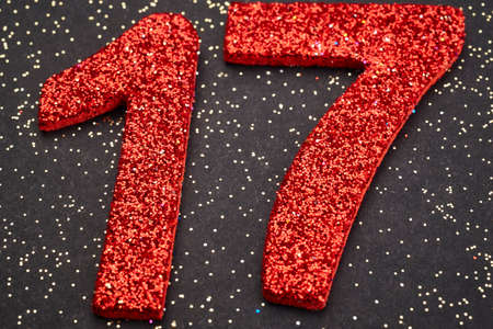 seventeen: Number seventeen red color over a black background. Anniversary. Horizontal