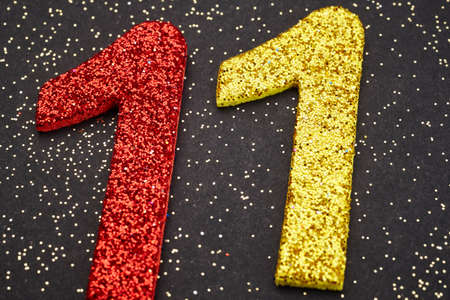 number 11: Number eleven red yellow color over a black background. Anniversary. Horizontal