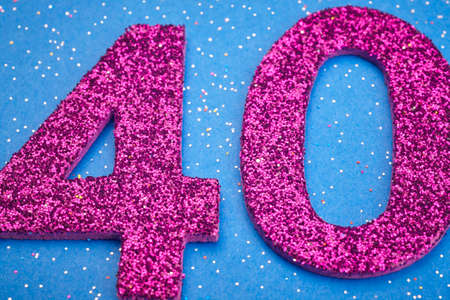 40: Number thirty purple color over a blue background. Anniversary. Horizontal Stock Photo