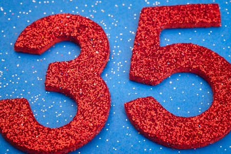 3 5 years: Number thirtyfive red color over a blue background. Anniversary. Horizontal Stock Photo