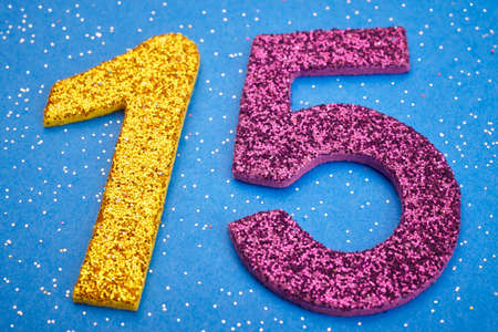 age 5: Number fifteen yellow purple color over blue background. Anniversary. Horizontal Stock Photo