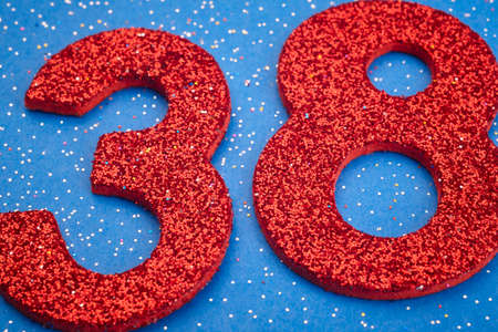 8 years birthday: Number thirtyeight red color over a blue background. Anniversary Stock Photo
