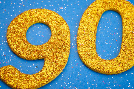 ninety: Number ninety yellow color over a blue background. Anniversary. Horizontal Stock Photo