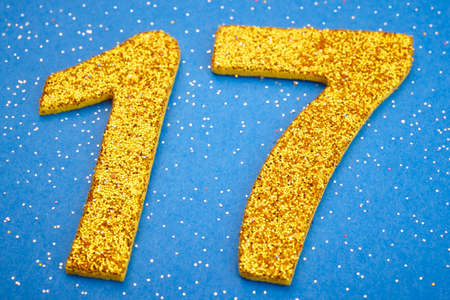 seventeen: Number seventeen yellow color over a blue background. Anniversary. Horizontal Stock Photo