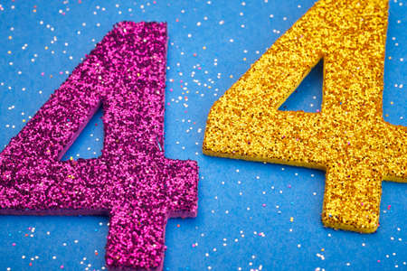 40: Number fortyfour purple yellow color over a blue background. Anniversary. Horizontal Stock Photo