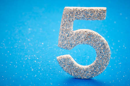 age 5: Number five silver color over a blue background. Anniversary. Horizontal Stock Photo