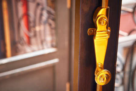 Golden metallic window lock detail with out of focus background. Horizontal Stock Photo