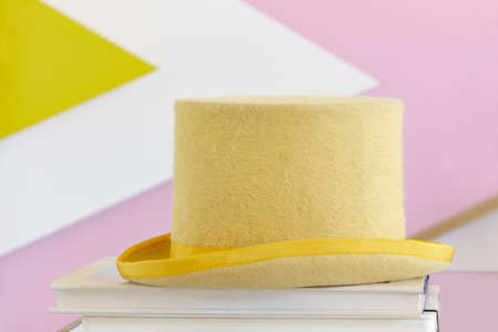 dressy: Yellow top hat still life with books and painted wall. Fancy party