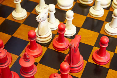 game over: Chess pieces in red and white color over the table. Play game Stock Photo