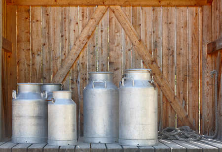 milk containers: Metallic milk containers on a wooden background. Farming. Horizontal