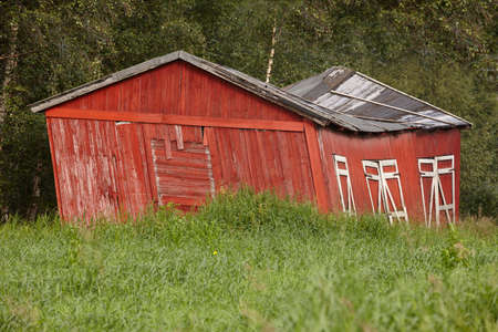 oddity: Norway. Red wooden rustic abandoned and curved farm house countryside. Horizontal