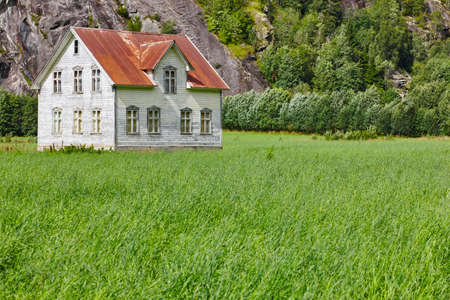 rust red: Norwegian antique traditional wooden house with grass and mountain. Horizontal Stock Photo
