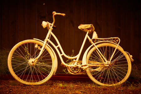 White old rusty bike in warm golden tone. Vintage background. Horizontal