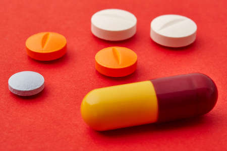 medicament: Pills over a red background. Medicament treatment. Health care photo Stock Photo