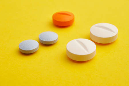 medicament: Pills over a yellow background. Medicament treatment. Health care photo