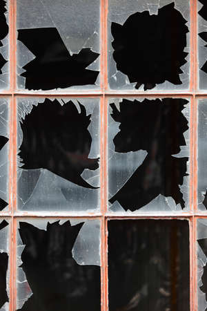 Damage window with broken glass and dark background. Vertical