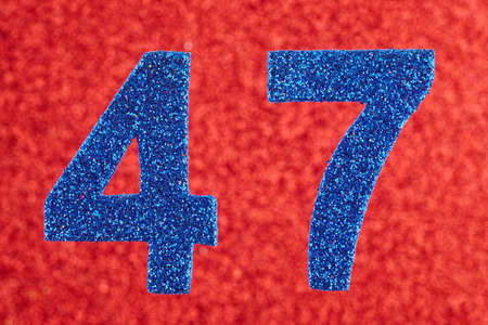 Number forty-seven blue color over a red background. Anniversary. Horizontal 免版税图像