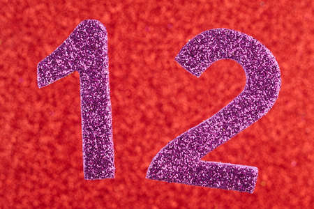 number twelve: Number twelve purple color over a red background. Anniversary. Horizontal Stock Photo