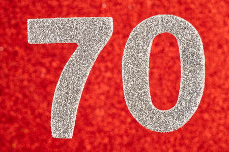 Number seventy silver color over a red background. Anniversary. Horizontal Stock Photo