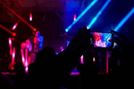 Smartphone video photo recording. Live concert by night. Horizontal Stock Photo